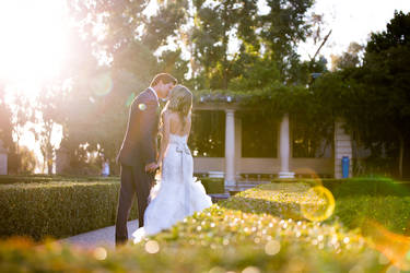 Portrait of a beautiful couple kissing on their wedding day. Sun flare.
