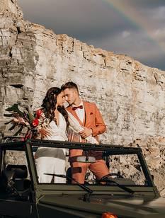Das Hochzeitspaar befindet sich auf einem Geländewagen und schaut sich verliebt in die Augen. Im Hintergrund ist die Location - ein Steinbruch - zu sehen